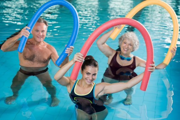 Portrait of smiling people doing aqua fitness together in a swimming pool. Group of senior woman and mature man with swim noodles exercising in a swimming pool. Young trainer and senior people in aqua gym fitness class.